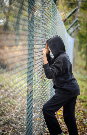 hooded shirt: wire fence in front sad young man standing