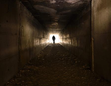 Człowiek chodzenie samotnie w ciemnym tunelu