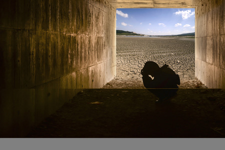 misery: Crying child in tunnel and dry cracked ground Stock Photo