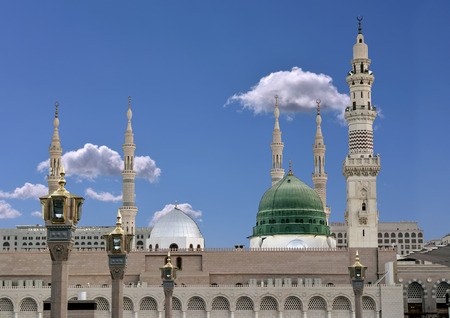 Exterior view of minarets and green dome of a mosque taken off the compound. 에디토리얼