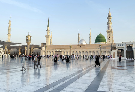 MEDINA, KINGDOM OF SAUDI ARABIA (KSA) - JAN 30: Muslims marching in front of the mosque of the Prophet Muhammad on January 30, 2015 in Medina, KSA. Prophets tomb is under the green dome.