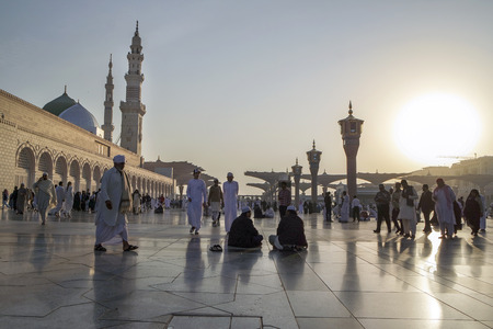 worshiped: MEDINA, KINGDOM OF SAUDI ARABIA (KSA) - JAN 30: Muslims marching in front of the mosque of the Prophet Muhammad on January 30, 2015 in Medina, KSA. Prophets tomb is under the green dome.