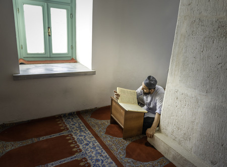 beanies: Muslim man reading the Holy Quran