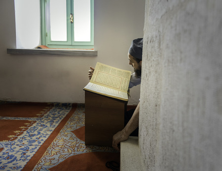 establishing: Muslim man reading the Holy Quran