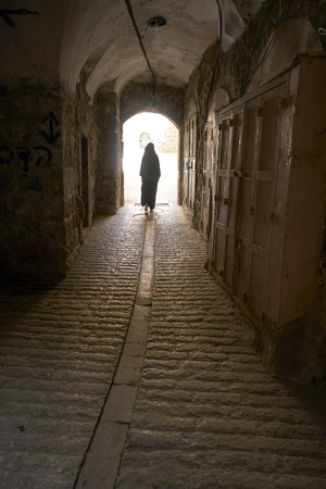woman walking a narrow path in Hebron (el-halil), Jarussalem.