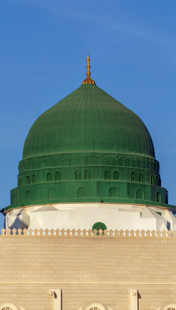 An external image of the Prophets Mosque in Medina in Saudi Arabia, It shows the minarets and green dome and sliver dome of the mosque.