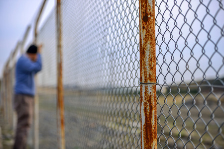 wire fence in front sad poor man standing Stock Photo