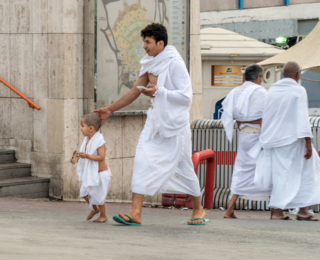 worshiped: MECCA, SAUDI ARABIA - JAN 28: Muslim man and kid wearing ihram clothes and ready for Hajj on January 28, 2017 in Mecca, Saudi Arabia. Muslims all around the world face the Kaaba during prayer time.