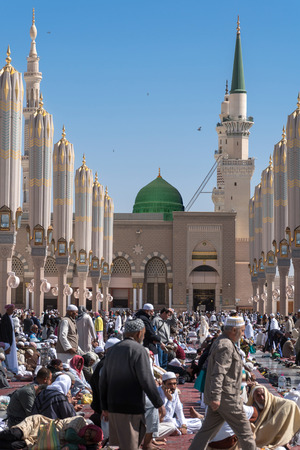 MEDINA, KINGDOM OF SAUDI ARABIA (KSA) - FEB 2: Muslims in front of the greeting gate mosque of the Prophet Muhammad on February 2, 2017 in Medina, KSA. Prophets tomb is under the green dome.