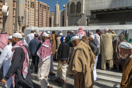 MEDINA, KINGDOM OF SAUDI ARABIA (KSA) - FEB 02: Pilgrims pray outside Masjid Nabawi after morning prayer February 02, 2017 in Medina, KSA. The mosque is the second holiest mosque in Islam.