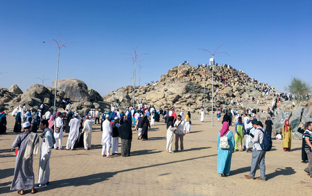 overthrown: MECCA, SAUDI ARABIA - JAN 29: Muslims at Mount Arafat (or Jabal Rahmah) January 29, 2017 in Arafat, Saudi Arabia. This is the place where Adam and Eve met after being overthrown from heaven.