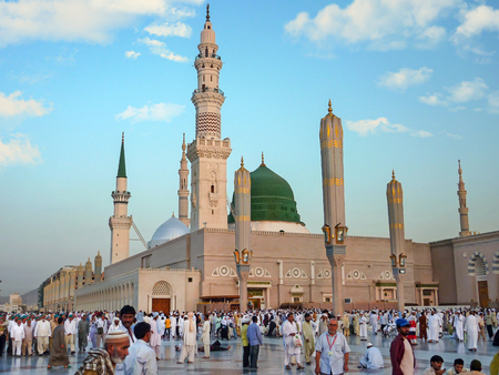 MEDINA, SAUDI ARABIA - SEPTEMBER 7: Muslims marching in front of the mosque of the Prophet Muhammad on September 7, 2010 in Medina, KSA. Prophets tomb is under the green dome.