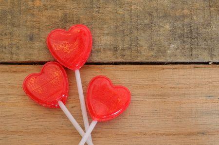 Heart shaped lollipops in floral design on wood pallet photo