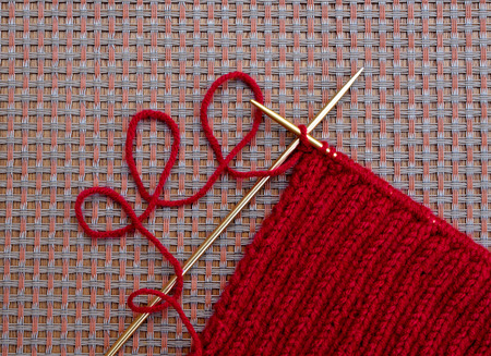 Knitting needles with knit scarf