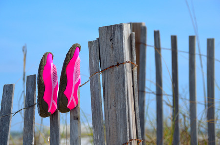 swim shoes: Swim shoes on wooden fence at beach sand dunes