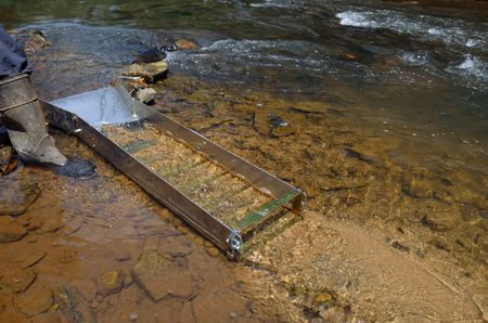 Gold panning with a sluice box in a river Stock Photo