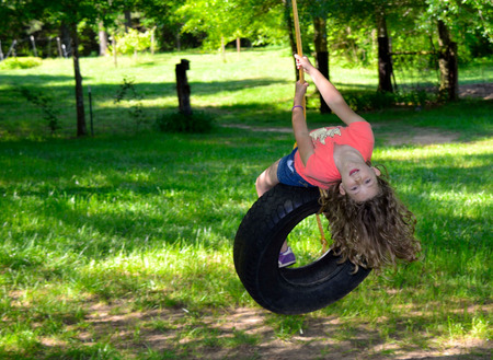 curly hair child: Young girl playing on a tire swing