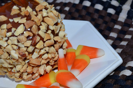 caramel candy: Caramel Apple covered with nuts, served with candy corn. Stock Photo