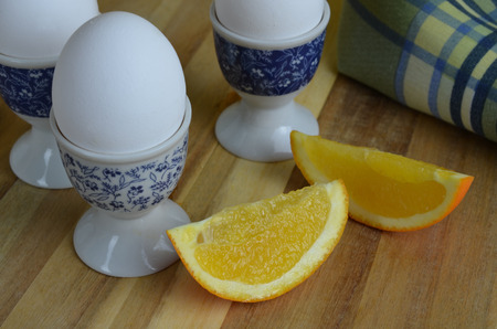 egg cups: Orange slices with soft boiled eggs in egg cups Stock Photo