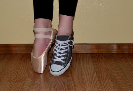Ballet shoe and tennis shoe, both worn by dancer standing on tiptoes