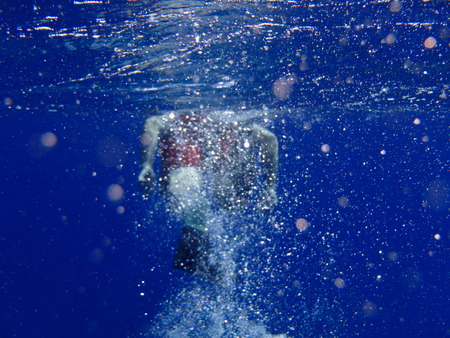 brilliant   undersea: Air bubble created by snorkeler in brilliant blue warm tropical ocean water