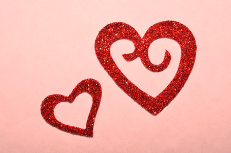 Red sparkling hearts on pink background. Romantic heart for Valentines Day or Wedding.