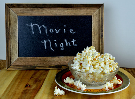 Fresh popped homemade hot buttered popcorn served in a bowl.  A sign suggesting movie night in the background.