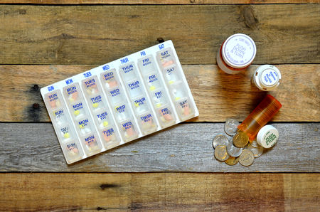 pillbox: Pillbox with medicine.  Medicine bottles with coins spilling out. Concept of high cost of medicine. Stock Photo