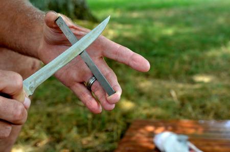 Man sharpening knife using a carbide block stick. Preparing utensil to fillet fish.