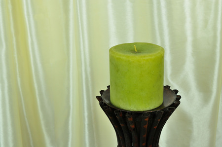 candle holder: Ornamental green candle on bamboo holder with silk background. Stock Photo