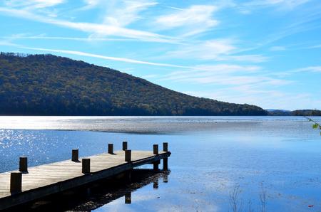 extending: Wooden dock extending over blue lake water
