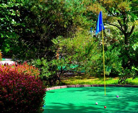 putt: Putt putt miniature golf course.  Turf, flag and balls on outdoor fun family sport. Stock Photo