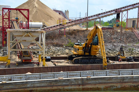 worksite: Industrial equipment unloading product from shipping barge