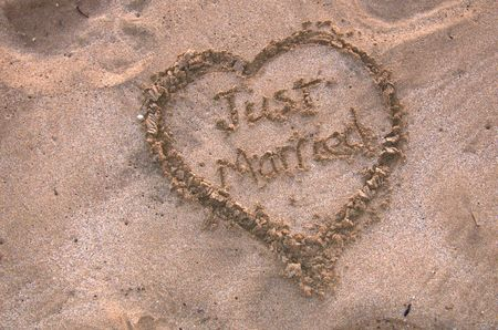 Just married surround by heart in soft tropical sand