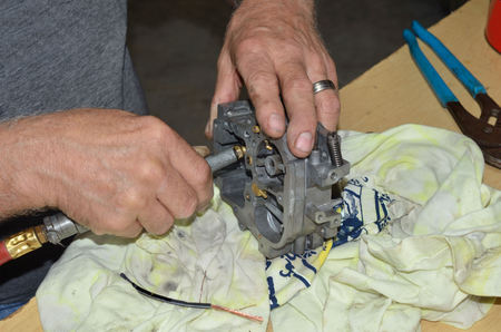 carburetor: Mans hands using tools to repair carburetor.  Truck carburetor in need of cleaning and replacement of parts.