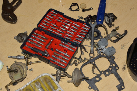 carburetor: Tools spread out on work table to clean and repair truck carburetor