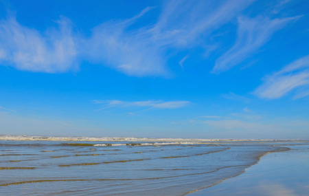wispy: Scenic ocean waves and sand, blue skies with wispy clouds