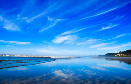 wispy: Wispy white clouds reflecting on wet sands of a Pacific Northwest ocean beach shoreline. Stock Photo