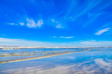 wispy: Pacific northwest coast shoreline.  Wispy clouds reflecting on wet sands. Stock Photo