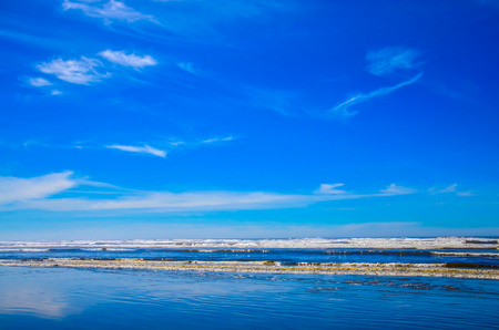 wispy: Pacific northwest ocean beach shoreline.  Saltwater waves splashing on shore.  Wispy white clouds in the vibrant blue skies.