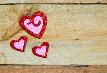 Sparkle, twinkle, glitter of red and pink hearts on pallet wood.  Valentines Day, Wedding, anniversary, symbol of love.