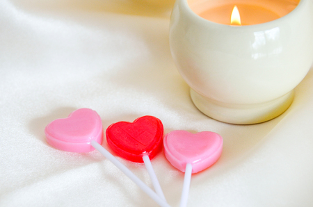 universal love: Romantic setting of lit candle with pink and red hearts on silk.  Valentines day, wedding, anniversary, universal symbol of love.