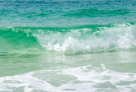 Tropical warm ocean waves splashing onto shoreline.  Tourist destination location. 版權商用圖片