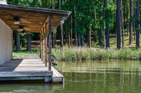 backwater: Scenic boat and swim dock located on reflective lake water. Recreational scenic location. Stock Photo