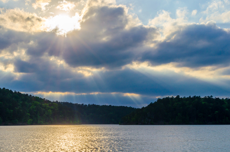 thru: Sun rays streaming thru dramatic clouds. Silhouette of mountain hills in the distance. Sunshine reflecting off of sparkling lake water.