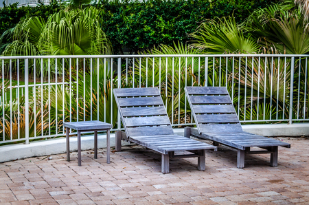 Rustic wooden deck chairs in tropical setting.  Enjoy the outdoors relaxing in lounge chairs surrounded by tropical palm trees. Stock Photo