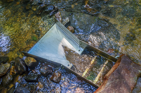 Sluice box, gold panning equipment.  Mineral rich soil flowing through with stream waters. Fun and adventure of prospecting and gold panning for gold and gemstones.