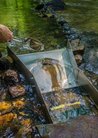 Sluice box for gold panning. Mineral rich material being fed into sluice box. Fun and adventure in prospecting and panning for gold.