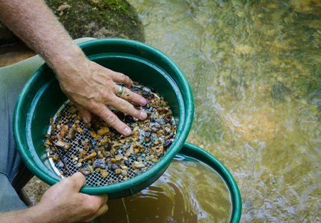 Gold panning and gem mining. Classifier used to sift material. Tools used for prospecting and panning for gold. Fun and adventure in this recreational activity. 版權商用圖片 - 85556574