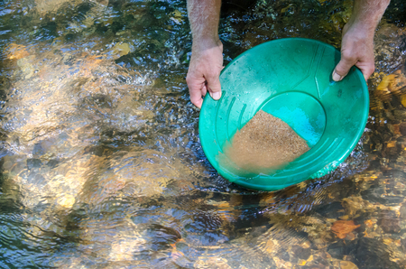 Gold pan filled with mineral rich material. Fun and adventure prospecting for gold and gemstones. Stock Photo